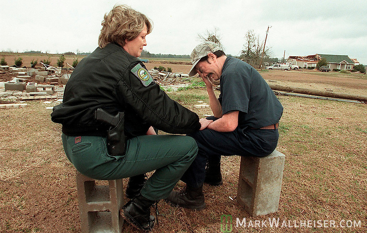 Georgia Department of Natural Resourses Ranger Sue Furney (L) comforts Jaime Chong-Chaparro after an early morning tornado ripped through the Pine Level Community north of Cairo on Valentines Day killing his fiance who lived in the trailer that used to be located on the cinder blocks at left.  Furney came by and spotted Chong-Chaparro sitting on one of the cinderblocks from the completely destroyed trailer alone and stopped to listen to him tell of his love for his fiance.  &quot;She will be in my heart forever&quot;, said Chong-Chaparro, adding, &quot;she is with the angles.&quot;