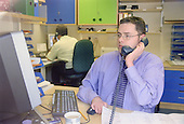 Man with disability, who is wheelchair user, working at computer in office talking on telephone.  MR