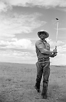 cowboy golfing in a field by himself