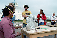 Inuvik, NWT, Northwest Territories, Arctic Canada - Inuit (Eskimo) Artist carving Soapstone Sculpture outside the Igloo Church (Our Lady of Victory)