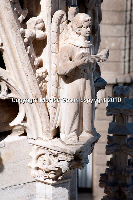 A sculpture of an angel with a lute or guitar on the roof of the Duomo (Cathedral) in Milan, Italy.