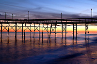 An ocean pier stands out from a dramatic sky of orange, blue and purple that are reflected in the atlantic in Ocean Isle Beach, North Carolina.