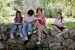 First graders sitting on a stone wall studying