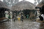 LALIYA, UGANDA MAY 26: Children play outside huts in a heavy rainfall on May 26, 2005 in Laliya, a poor rural village in northern Uganda. Many children in this area are afraid of being abducted by the Lord's Resistance Army (LRA). The rebel group has brought terror to Northern Uganda for almost twenty years, fighting the Ugandan government. The victims are usually children, which are abducted and used as child soldiers and sex slaves. About 1.5 million people have fled villages and live in about 180 squalid Internally Displaced People (IDP) camps, which has changed the rural life in Northern Uganda. About 20,000 children walk every day to the nearby provincial capital Gulu where NGO:s house the children. Many children are too afraid to sleep in the villages. (Photo: Per-Anders Pettersson)..