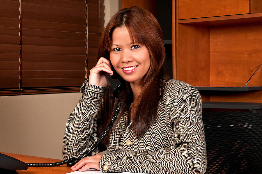 A friendly worker talking in the phone with a client in a small business setting.