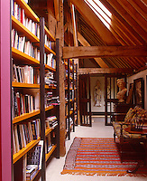Lit by a skylight, a library is situated under the ancient exposed beams of the roof space in this converted barn