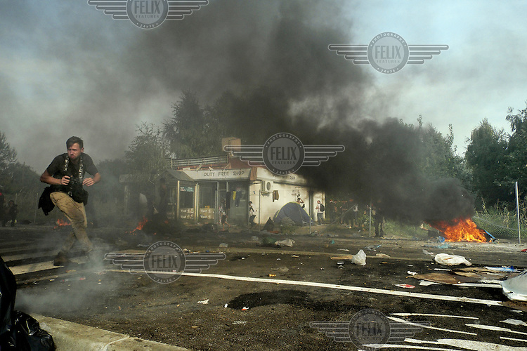 Photographer Maciej Moskwa runs to safety as Hungarian riot police fires tear gas and water cannon at people trying to cross the border from Serbia. The newly completed razor wire fence that, as of 15 September 2015, sealed the border with Serbia leaving thousands of migrants and refugees stranded outside the European Union.