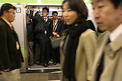 Commuters pack onto a Yamanote Line train, during rush hour, Tokyo, Japan.