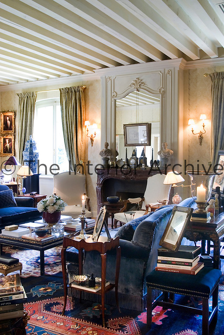 The living room is furnished with blue velvet sofas and is cluttered with family memorabilia