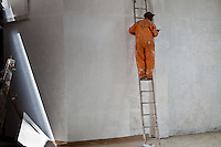 A painter spackling a wall at Nairobi University in Kenya.