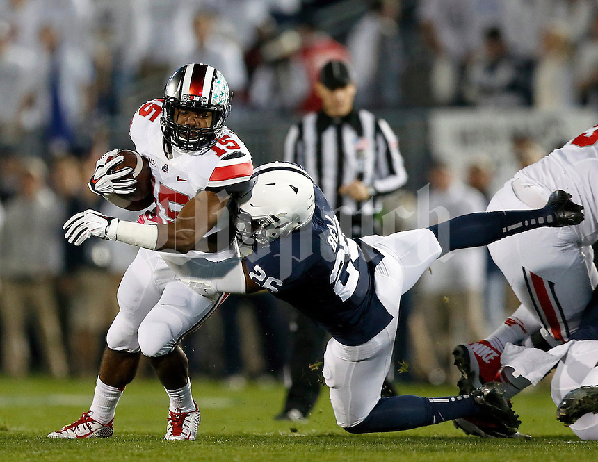 Ohio State Buckeyes running back Ezekiel Elliott (15) tries to get away from Penn State Nittany Lions linebacker Brandon Bell (26) during the first quarter of the NCAA Division I football game at Beaver Stadium in University Park, PA on October 25, 2014. (Columbus Dispatch photo by Jonathan Quilter)