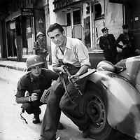 American officer and French partisan crouch behind an auto during a street fight in a French city, ca.  1944. (Army)<br /> Exact Date Shot Unknown<br /> NARA FILE #:  111-SC-217401<br /> WAR &amp; CONFLICT BOOK #:  1055