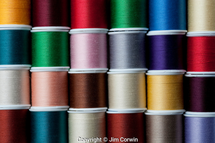 Close-up of multicolored spools of thread in rows