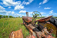 This junkyard in the western Minnesota prairie was very large and mostly covered by high grass. In this section of farm equipment there was a lot of extra room, so the tractors were set down anywhere; you can see others poking up here and there all around. This particular one drew my attention because of the little sprig bravely reaching for the wild blue yonder from the steering wheel, which gave this image a title. Determination or The Resiliency of Hope might have made a good one too. Here was the carcass of a hardworking machine with its bones bleaching in the sun forevermore, but there is new life reaching out from the remains of the old, like a seed. Its hard to stop Mother Nature and here&rsquo;s proof again of that fact. So, curiosity piqued, I waded on over through the tall grass for a closer look as to what could be done with a wide angle lens and that even wider prairie sky.<br />