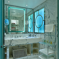 This contemporary bathroom is lined with white marble and the frosted glass windows are encased in polished chrome frames