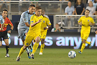 Columbus Crew midfielder Robbie Rogers (yellow) moves away from Davy Arnaud, Sporting KC... Sporting Kansas City defeated Columbus Crew 2-1 at LIVESTRONG Sporting Park, Kansas City, Kansas.