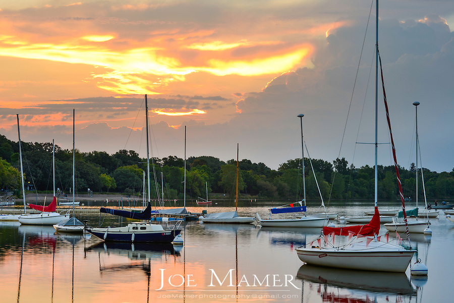 Sailboats moored at Lake Harriet during a summer morning sunrise with storm clouds moving in.