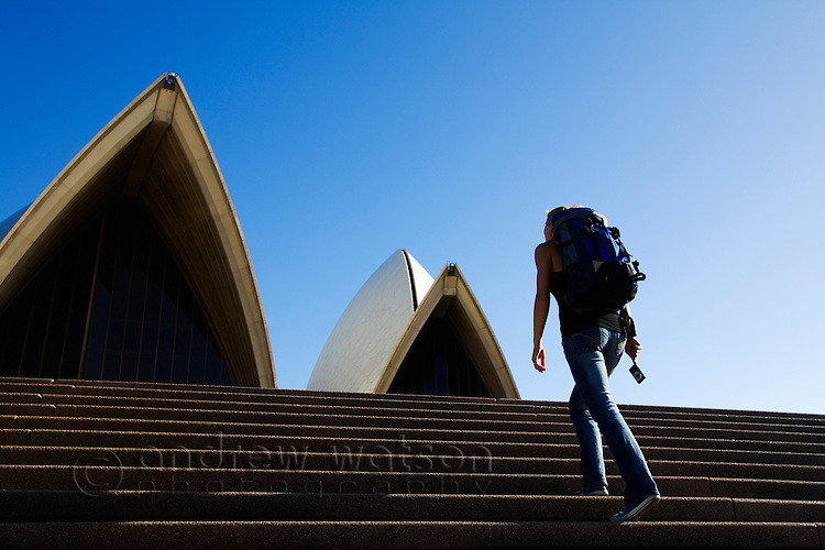 A backpacker climbs the steps of the Sydney Opera House.  Sydney, New South Wales, AUSTRALIA.
