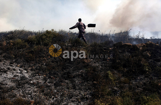 A Palestinian firefighter try to extinguish a fire in the West Bank town of Aseera al-Qabliya, near Nablus, Tuesday, April 30, 2013. In the West Bank, a Palestinian man fatally stabbed an Israeli waiting at a bus stop and fired on police before he was detained by Israeli security forces, officials said. The Israeli military said that following the stabbing settlers began rioting, hurling rocks at Palestinian vehicles and setting fire to nearby fields. Photo by Issam Rimawi