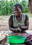 "A woman removes the kernels from corn in Chisatha, a village in southern Malawi. Her community has been hard hit by drought in recent years, leading to chronic food insecurity, especially during the ""hunger season,"" when farmers are waiting for the harvest."