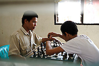 A blind adult and teenage boy playing chess, Makassar, Sulawesi, Indonesia.