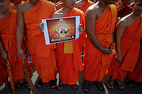 A Buddhist monk holds a picture of the former king Norodom Sihanouk  as he join thousands of mourners waiting for a royal hearse to arrive to the Royal Palace in Phnom Penh October 17, 2012. Tens of thousands poured into Cambodia's capital to witness the procession on Wednesday of the body of Sihanouk, a revered figure who ruled through the triumph of independence to the tragedy of its brutal civil war. Mourners dressed in white lined the 10-km (6-mile) route to welcome the return of Sihanouk, the flamboyant former monarch who died at 89 of heart failure on Monday in Beijing, his residence since abdicating eight years ago. REUTERS/Damir Sagolj (CAMBODIA)