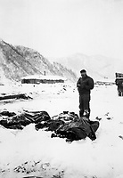 A wounded chaplain reads a memorial service over the snow-covered bodies of dead Marines.  Koto-ri, Korea.  December 3, 1950.  Cpl. W. T. Wolfe.  (Marine Corps)<br /> NARA FILE #:  127-N-A5552<br /> WAR &amp; CONFLICT BOOK #:  1512