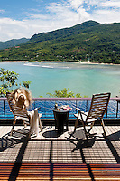 A stunning view of the lush Mahe' hills and the Anse Louis beach from a private balcony at the Maia Luxury Resort & Spa