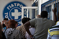 Refugees and migrants queue for a free primary care clinic run by Medicins du Monde in the Omonia district of Athens 12-6-12