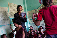 Chandraseker Shahi, 17, sings a self-written song against child marriage while Ganga Regmi (right, pink, age 10) and another member dance to it at the Kishuri Sachetana Child Club in their activity center in Thahuri Tole, Chhinchu, Surkhet district, Western Nepal, on 1st July 2012. Ganga Regmi is Pandit Dharma Raj Regmi's daughterand has ambitions to be a doctor. These Child Clubs, supported by the government, Save the Children and their local partner NGO Safer Society, advocate for child rights and against child marriages and use peer support and education to end child marriages and raise awareness. Photo by Suzanne Lee for Save The Children UK