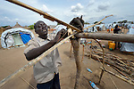 Gumbo Paul builds the framework for his family's tent in a camp for almost 500 internally displaced people located at the St. Vincent de Paul Catholic parish on the edge of Juba, the capital of South Sudan. The families here fled fighting that broke out in December 2013. More than 700,000 people have been internally displaced in the first three months. Paul, along with his wife and five children, came to Juba from Bentieu.