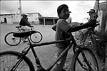Zapotec Native neighbors stand next to their bikes on a street in Coatecas Altas village, Oaxaca, November 22, 1998. Most of the villagers of Coatecas leave their home to harvest in northern state of Sinaloa.  © Photo by Heriberto Rodriguez