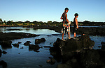 Two boys fish with a new from atop the rocks into the low-tide pools about Na alehu on the south side of the Big Island of Hawaii.