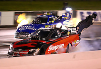 May 30, 2014; Englishtown, NJ, USA; NHRA funny car driver Cruz Pedregon (near) runs a 3.959 alongside Tommy Johnson Jr during qualifying for the Summernationals at Raceway Park. The run was the quickest in NHRA funny car history. Mandatory Credit: Mark J. Rebilas-