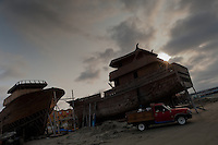 The unfinished wooden fishing vessels are seen during the sunset in an artisanal shipyard on the beach in Manta, Ecuador, 20 November 2014. The construction process takes 3-4 months to complete, depending on the ship size and purpose (fish capture methods). Although a wooden boat tends to be more stable on the sea and less expensive to build (up to $0.5 million USD), it needs a maintenance every 2 years, while a fiberglass-made boat, costing almost double the wooden one, may serve 5-6 years without any repairs. The shipyard produces 6-8 vessels every year.
