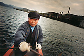 North Korea, 11-2003..A Chinese fisherman wades passes a North Korean factory along the 1,400-km North Korea-China border. (Exactly location cannot be revealed.)..China help North Korea fight the Korean War in the 1950s and continue to have a defence treaty with the Stalinist country.. .North Korea is the world's most insular and totalitarian state. Ruled by the messianic leader Kim Il Sung and his son Kim Jong Il since 1948, North Korea has stubbornly stuck to its juche (self-reliance) ideology and siege mentality, imposing one Stalinist economic plan after another. Floods, droughts and mismanagement in the 1990s plunged the country into a preventable famine, killing up to three million, or 13 percent of the population. It now depends heavily on Chinese aid...