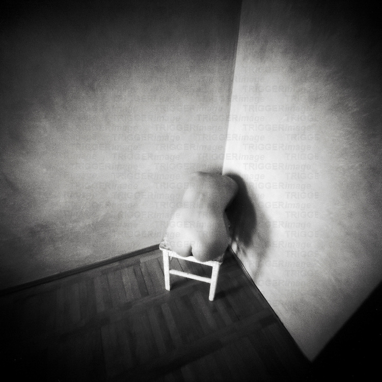A naked female figure sitting on a stool in the corner of an empty room