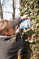Vogel-Futterhäuschen, wird von einer Frau mit Sonnenblumen-Kernen gefüllt, Futterhaus, Futterhäuschen, Vogelfutter
