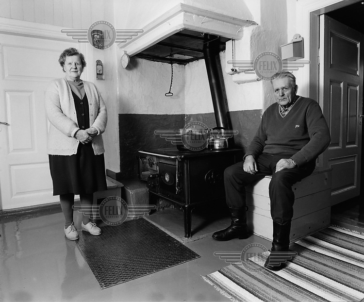 Old couple in the kitchen of their home.