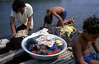 As their mother washes clothes in the river, two young boys play around a floating dock on the Rio Negro in Brazil's Pantanal — the world's largest wetland. Ecosystems and ways of life could be threatened there by a plan to dredge the Rio Paraguay to allow shipping access to land-locked Paraguay and Bolivia. Critics of the plan charge that dredging will alter the seasonal flooding patterns of the Kansas-sized wetland.