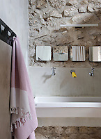 Four small mirrors are situated above the generously-sized stone sink in this child's bedroom
