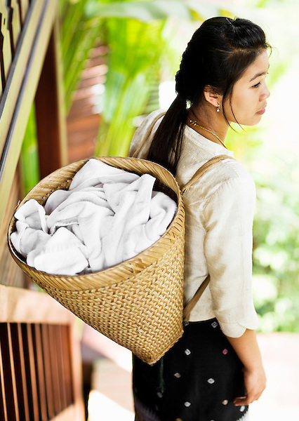 A chamber maid carries room towels in a basket on her back at 3 Nagas by Alila Hotel. Luang Prabang, Laos.