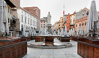 """Low angle view of Piazza delle Erbe, surrounded by closed umbrellas, Verona, Italy. The Piazza delle Erbe (Square of Herbs) stands on the old Roman Forum, and remains the centre of city life. In the centre of the square is a fountain built in 1368, perhaps by Bonino da Campione with a 4th century Roman statue, known as the """"Madonna Verona"""" and seen from behind on the picture. Picture by Manuel Cohen."""
