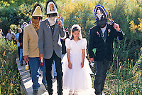 Wearing their veiled headresses and carrying ceremonial tridents, mysterious Matachine dancers and a young girl dressed as La Malinche all pause at the crossing of a stream for the  blessing of the water during the Sunday  morning procession at the Las Golondrinas Fall Festival near Santa Fe.