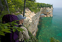 A backpacker looks out over the cliffs of Pictured Rocks National Lakeshore near Munising, Michigan.
