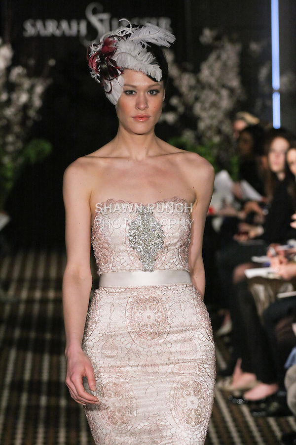 Model walks runway in an Amour wedding dress by Sarah Jassir, for the Sarah Jassir Fall 2011 - Desire bridal collection.