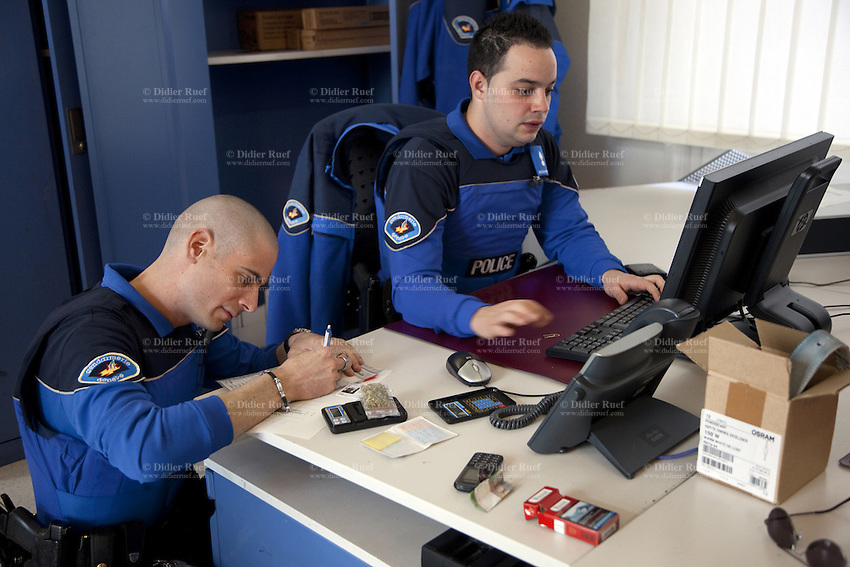 Switzerland. Geneva. Paquis police station. Two police officers check on a computer the identity of a man who was arrested. A police station or station house is a building which serves police officers and contains offices, locker rooms, temporary holding cells and interview/interrogation rooms. Both policemen wear a ballistic vest, bulletproof vest or bullet-resistant vest which is an item of personal armor that helps absorb the impact from knives, firearm-fired projectiles and shrapnel from explosions, and is worn on the torso. Soft vests are made from many layers of woven or laminated fibers and can be capable of protecting the wearer from small-caliber handgun and shotgun projectiles, and small fragments from explosives such as hand grenades. 16.03.12 © 2012 Didier Ruef