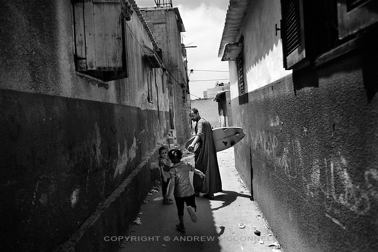Mohammed Abu Jayab, 38, guestures to his daughter as he walks from his home in Shati Refugee Camp, Gaza Strip. Abu Jayab is the leader of a surf group in Gaza and one of the pioneers of the sport in the coastal enclave.