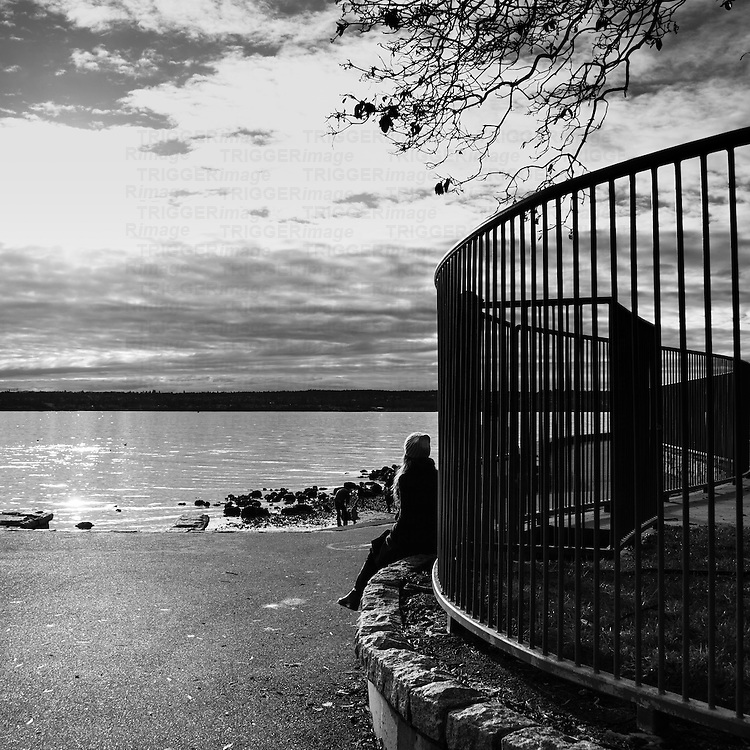 A lone woman sitting along a curved wall with a fence, watching people on the beach during winter.