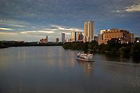 A cruise ship steams along Lady Bird Lake in downtown Austin, Texas.